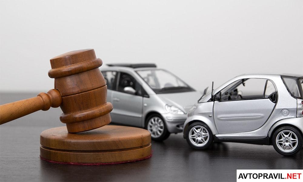 Судейский молоток и две игрушечные машины, стоящие на столе
