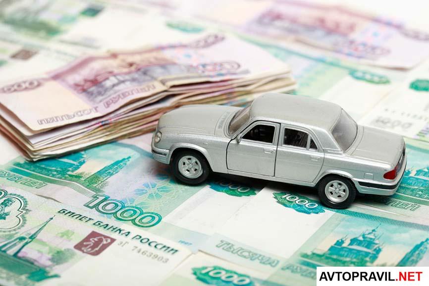 Игрушечный автомобиль, стоящий на фоне денег