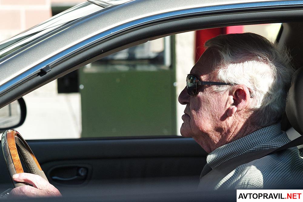 Пожилой человек, сидящий за рулем автомобиля