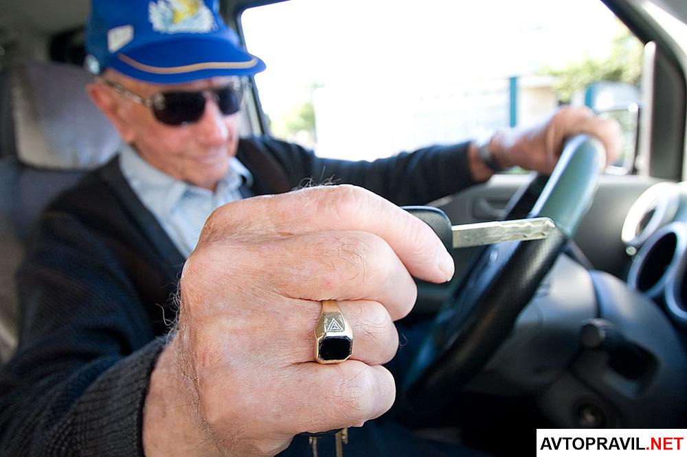 Пожилой мужчина, сидящий за рулем автомобиля и держащий ключи