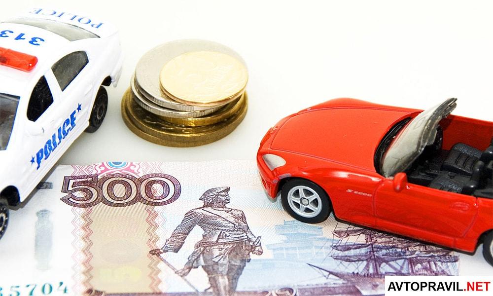 Два игрушечных автомобиля и рубли, лежащие на столе