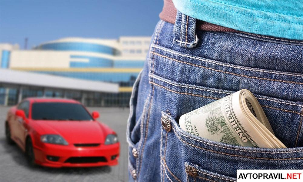 Деньги, лежащие в заднем кармане джинсов и красный автомобиль