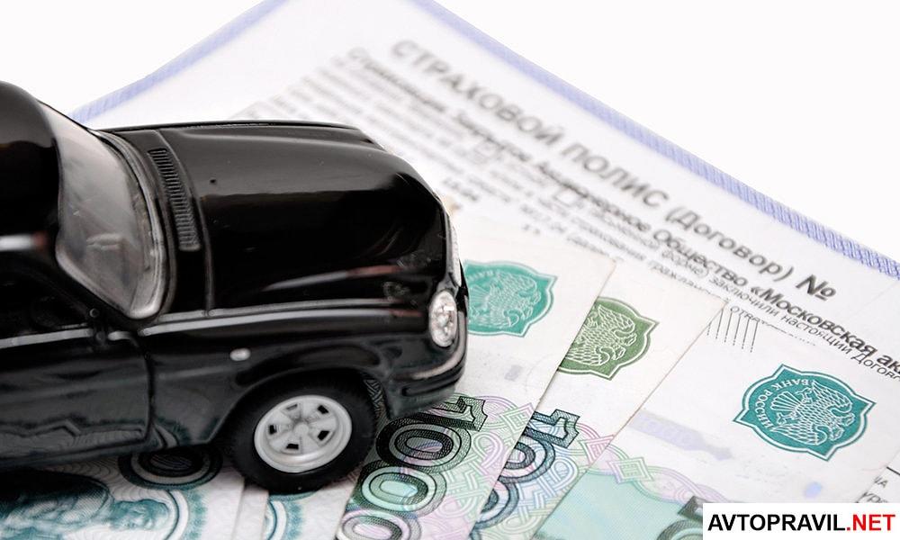 Игрушечный автомобиль, страховой полис и деньги, лежащие на столе