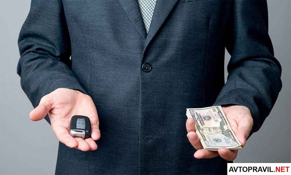 Человек в костюме, держащий в руках ключи и деньги